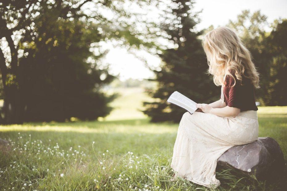 Uma mulher sentada em uma pedra num campo lendo um livro