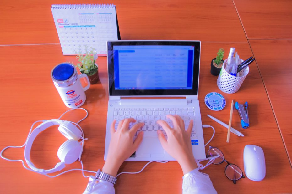 Uma mesa contendo fone de ouvido, caneca, mouse, porta lápis e mãos digitando em um computador vendo o linkedin