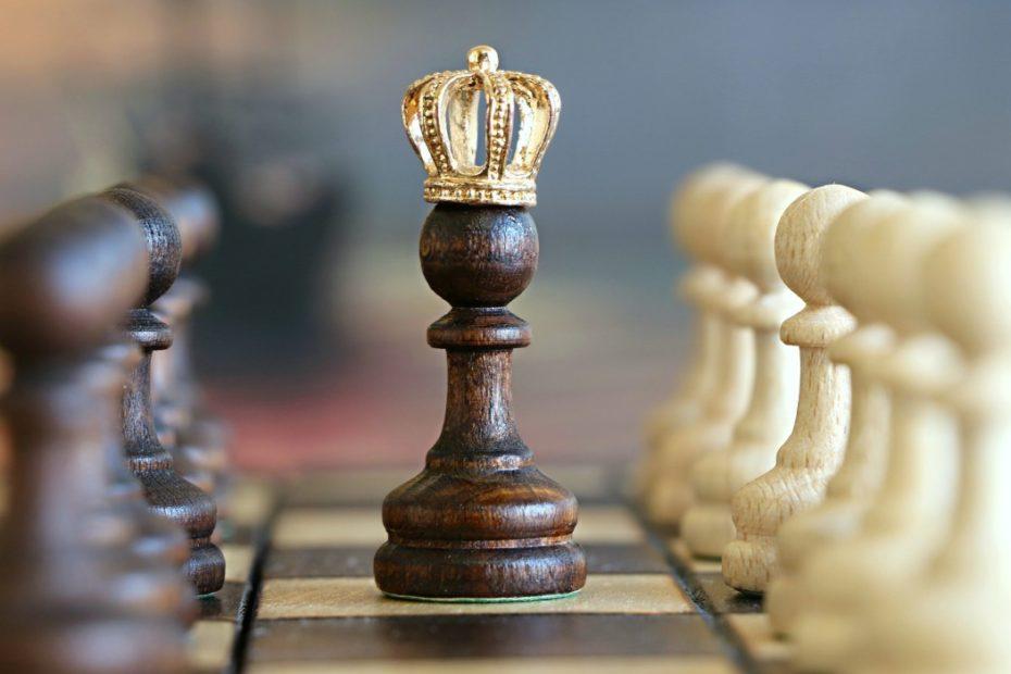 Na imagem aparece um tabuleiro de xadrez com um peça em destaque usando uma coroa de rei