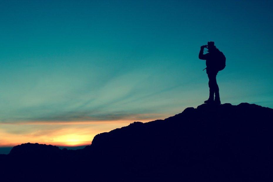 a imagem mostra um homem em cima de um morro avistando o céu e o futuro