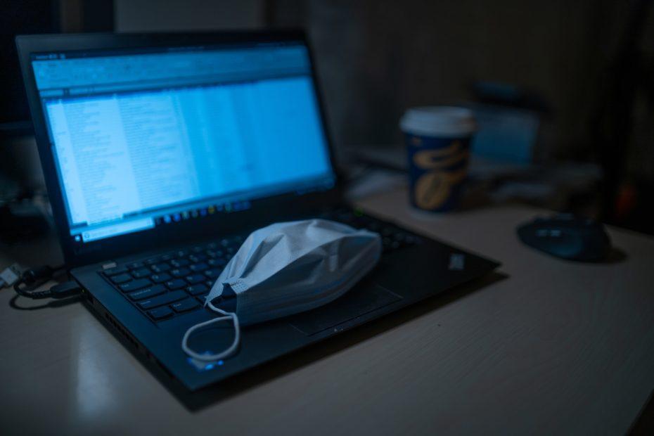 um computador aberto para definir uma comunicação digital com uma máscara em cima do teclado que significa a prevenção ao coronavírus