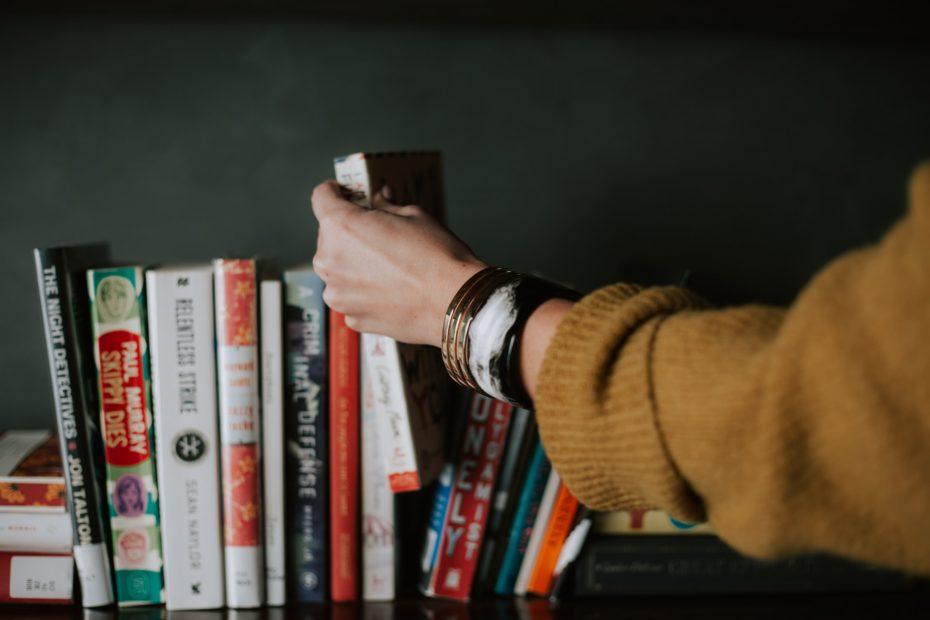 mulher pegando um livro sobre marketing de conteúdo na estande ontem mais livros sobre produção de conteúdo para web