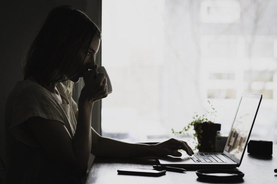 Um mulher tomando chá em frente do computador