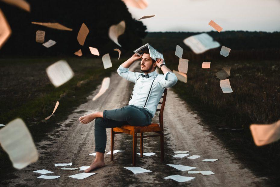 homem sentado na cadeira no meio de uma estrada segurando um livro e várias folha desse livro caindo como se fosse chuva