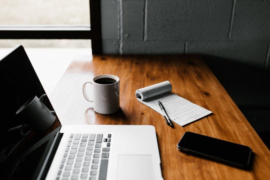 mesa com um notebook, caderno, caneta, celular e caneca com café