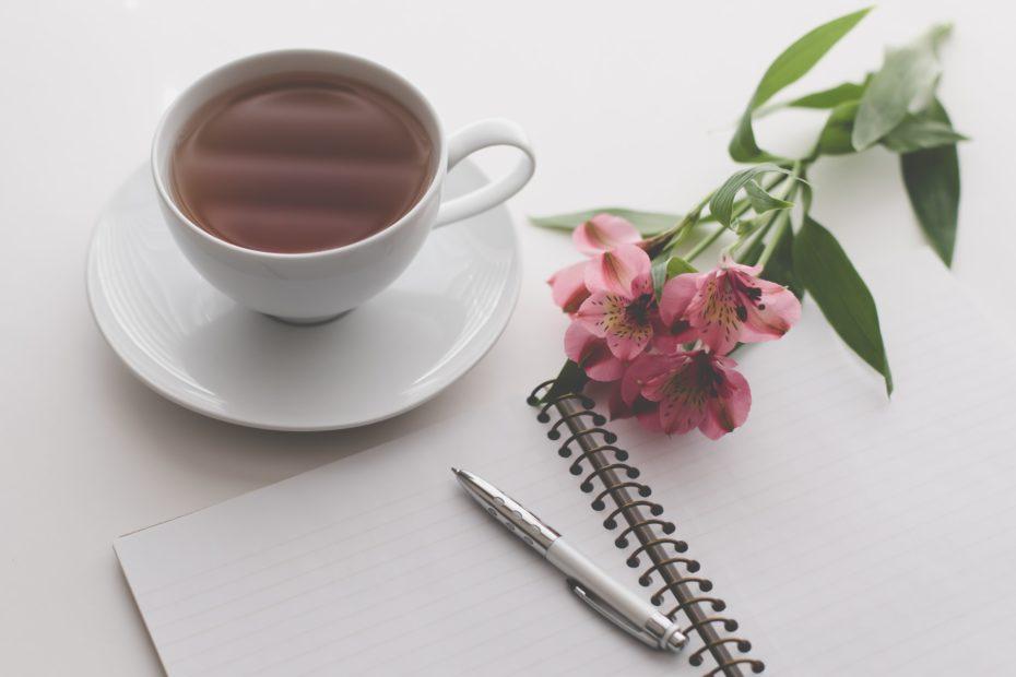 uma xicara de chá, um caderno com uma caneta em cima e um raminho de flores cor de rosa